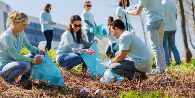 A volunteer picking up trash during a community clean up.