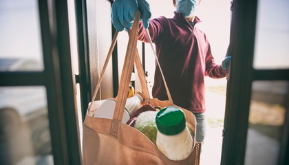 A volunteer delivering food to a home.