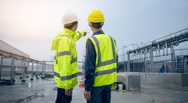 Two professionals wearing hard hats and reflective vests