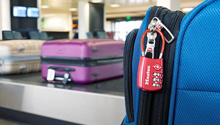 A piece of luggage at an airport baggage claim secured with a combination padlock