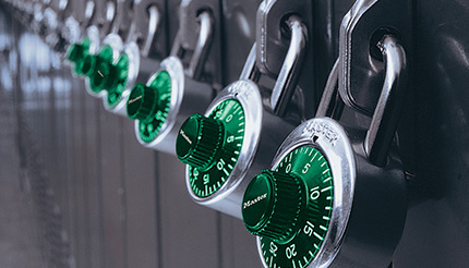 Padlocks with green dials on a row of lockers