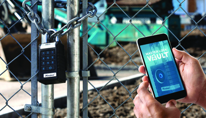 Master Lock Proseries padlock on gate with hand holding a phone displaying the Master Lock Vault app