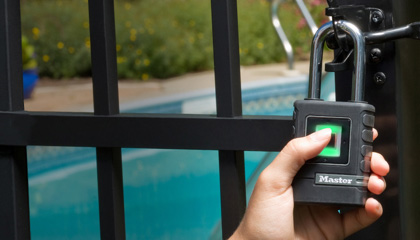 A hand with thumb pressed against a biometric padlock securing the door to an outdoor pool