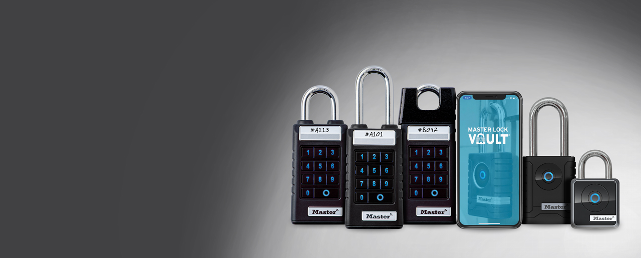 A collection of Bluetooth enabled hardware alongside a phone showing the Master Lock Vault Enterprise app